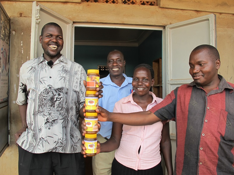 Image: Ojok Simon, at left,holds jars of honey and stands with his colleagues.
