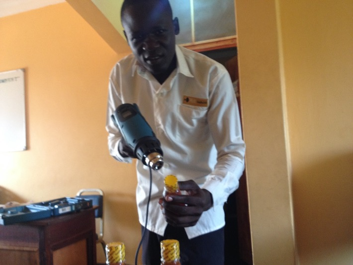 HIVE Uganda putting security seal using heat gun acquired