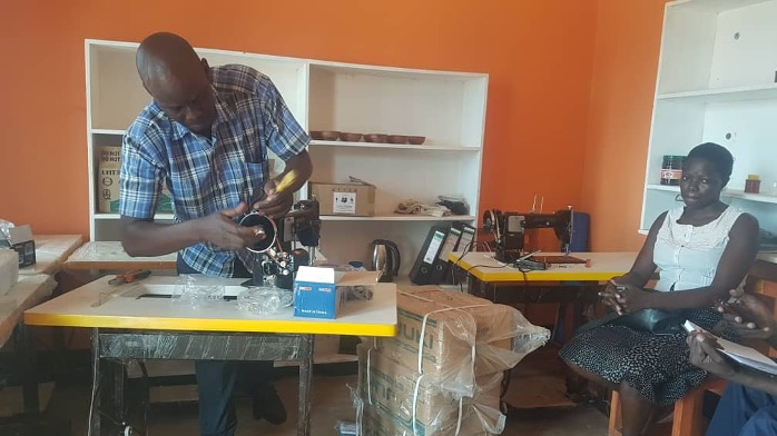 Trainer setting tailoring machines for training.